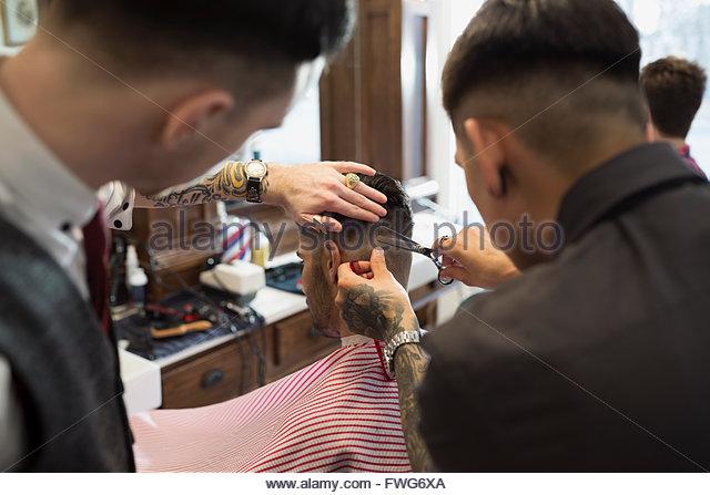 Barbers cutting man - Stock Image