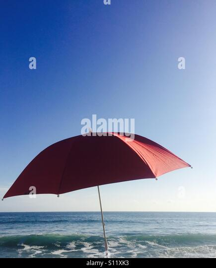A single red umbrella and the ocean and sky. Ventura, California USA. - Stock Image