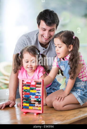 Happy father and daughters playing with abacus in house - Stock Image