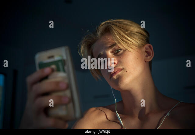 A good looking teenage boy taking a selfie with a mobile phone - Stock Image