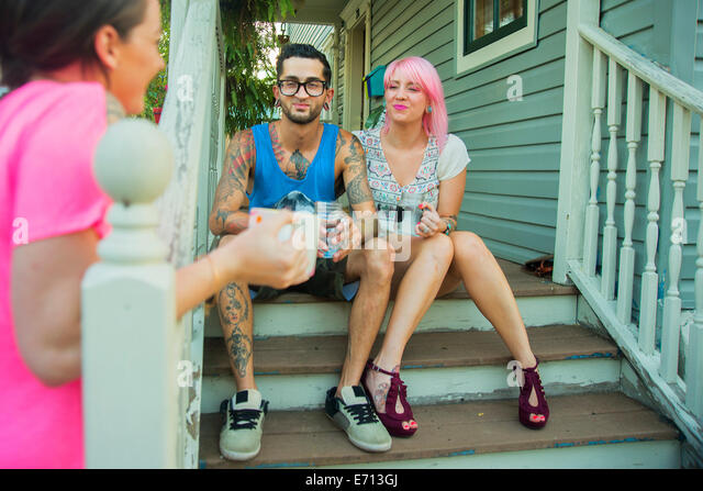 Young adult friends chatting on porch steps - Stock-Bilder