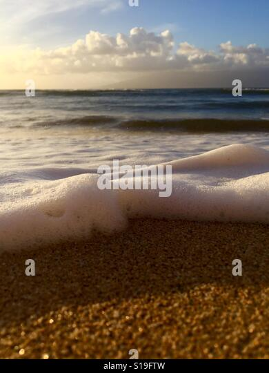 A wave rolling up on the shore at sunset. Kāʻanapali, Maui, Hawaii. - Stock Image