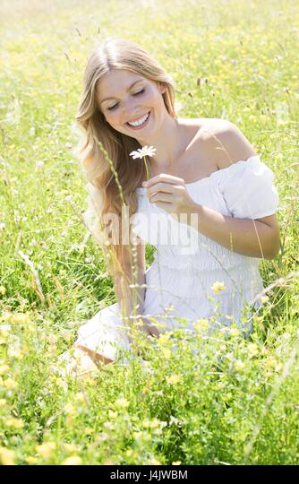 MODEL RELEASED. Young woman sitting in meadow holding daisy. - Stock-Bilder