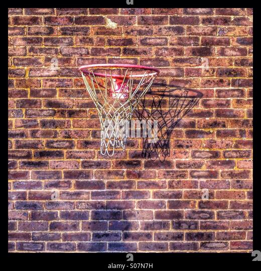 Netball net mounted on a brick wall - Stock Image