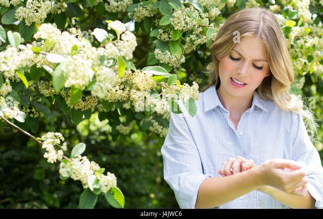 MODEL RELEASED. Young woman by tree scratching arm. - Stock-Bilder