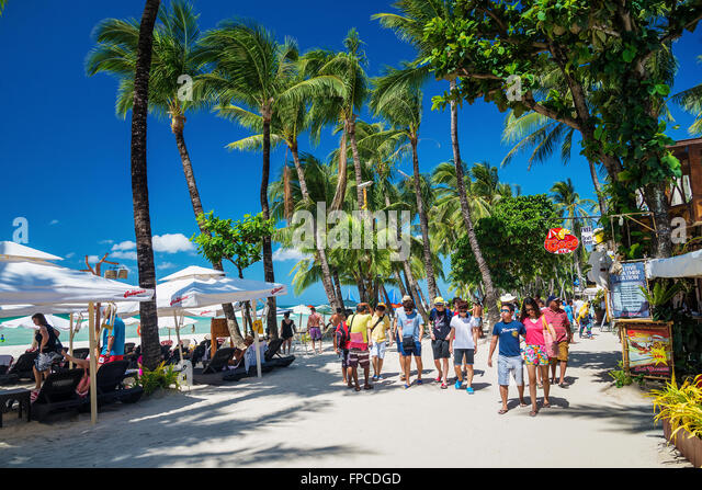 tourists on station 2 main beach busy shop restaurant street in boracay island philippines - Stock Image