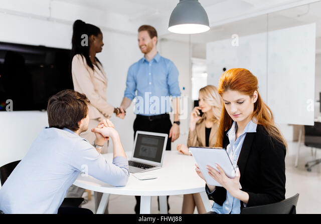 CEO of company holding tablet at board meeting while staff is discussing new strategy - Stock Image