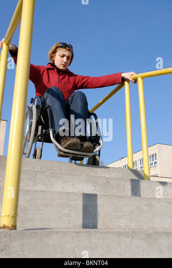 Handicapped woman on wheelchair going down the concrete stairs - Stock Image