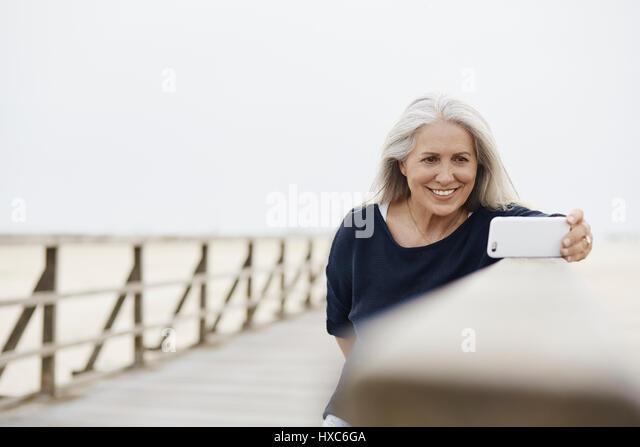 Smiling senior woman taking selfie with camera phone on beach boardwalk - Stock Image