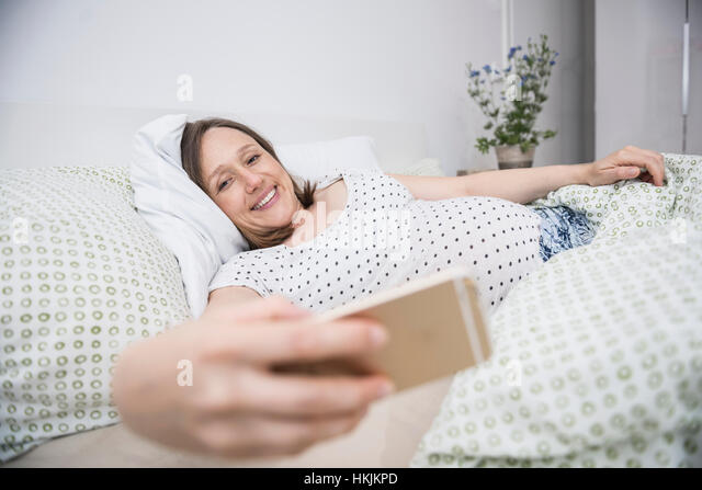 Pregnant woman lying in bed and taking selfie on mobile phone, Munich, Bavaria, Germany - Stock Image