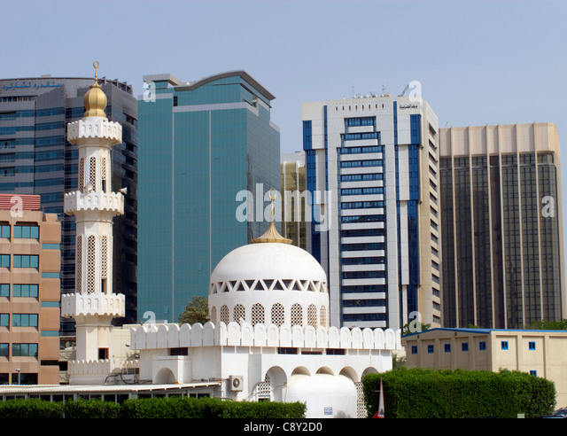 Contrast between mosque and new office buildings in central Abu Dhabi United Arab Emirates UAE - Stock Image