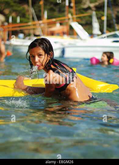 Spain, Barcelona, girl (8-9) playing in the sea - Stock Image