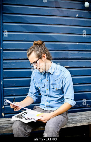 Young man looking at print outs of designs outside - Stock Image