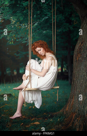 Beautiful thoughtful woman on a swing in the wood . Romantic and vintage portrait - Stock-Bilder