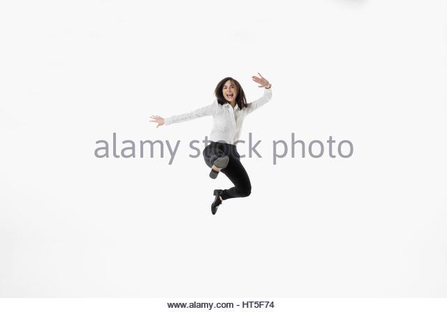 Portrait exuberant businesswoman jumping for joy against white background - Stock-Bilder