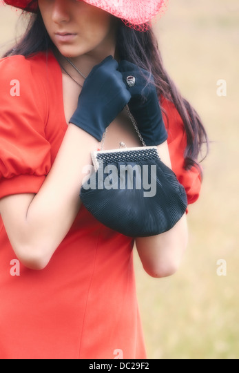 a woman in a red dress with a black handbag - Stock Image
