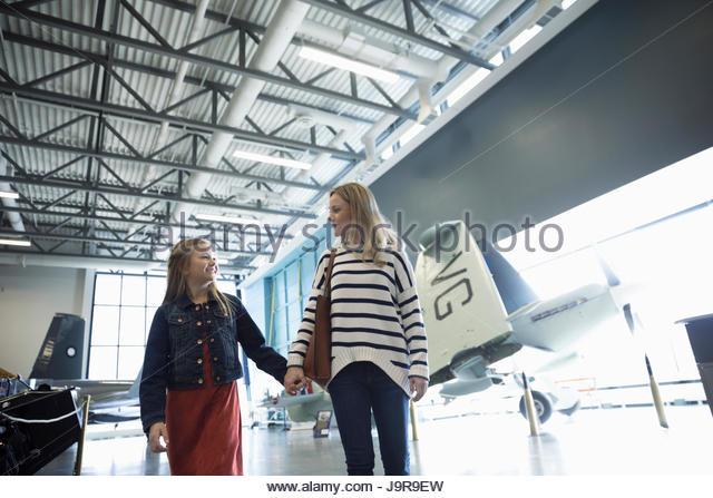 Mother and daughter walking, holding hands among airplanes in war museum hangar - Stock-Bilder
