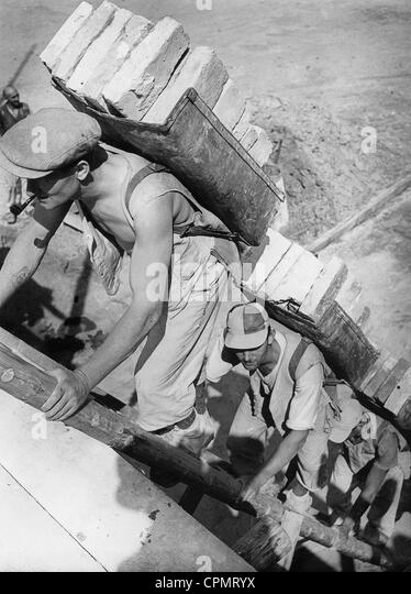 Workers carry bricks, 1939 - Stock-Bilder