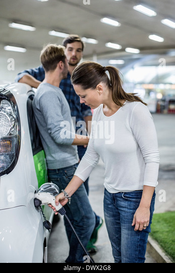 Woman charging electric car with friends standing in background at gas station - Stock Image