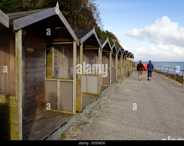 Beach huts and walkers on the coast path at Swanpool, Falmouth, Cornwall - Stock Image