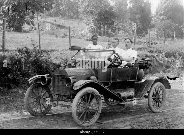 Full length portrait of two men driving a car outdoors, one African American child in the car, 1920. - Stock Image
