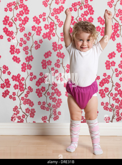 Toddler in front of colorful wall paper - Stock Image
