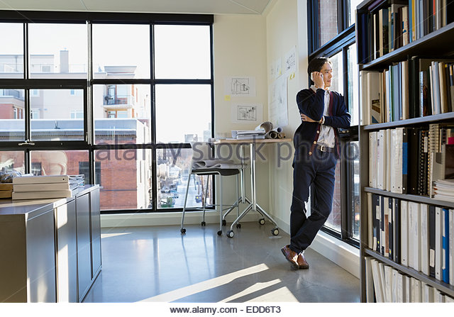 Businessman talking on cell phone at office window - Stock-Bilder