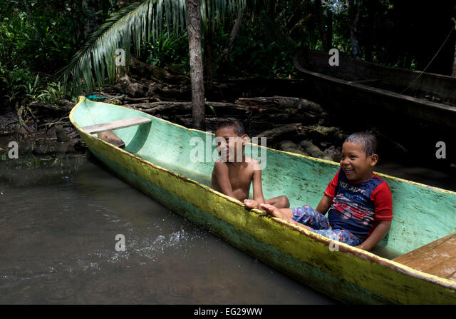 Kids play in one of the local boats used by the Ngobe Indians as their main form of transport, sheltered under a - Stock-Bilder