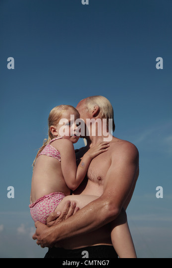 Low angle view of man carrying daughter (6-7) - Stock Image
