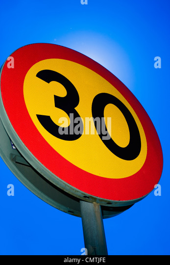 Speed limit sign against blue sky - Stock Image