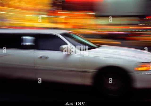 White Luxury Limousine Speeding City Lights at Night New York City USA - Stock Image