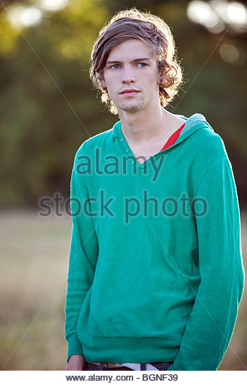 Portrait of a young man outdoors, thinking - Stock Image