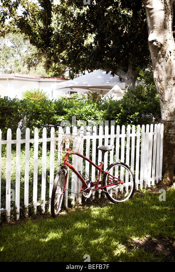 Bike leaning on fence - Stock Image