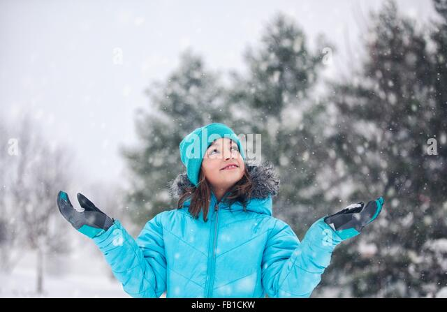 Girl wearing turquoise knit hat and coat, arms raised, hands out catching snow, looking up smiling - Stock Image