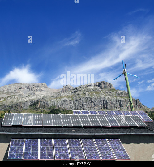 solar plates and windmill under blue sky green energy - Stock Image