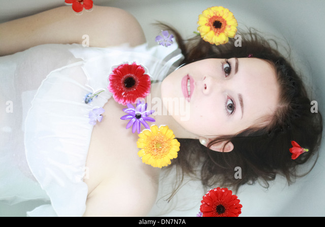 Young woman with flowers in the bathtub - Stock Image