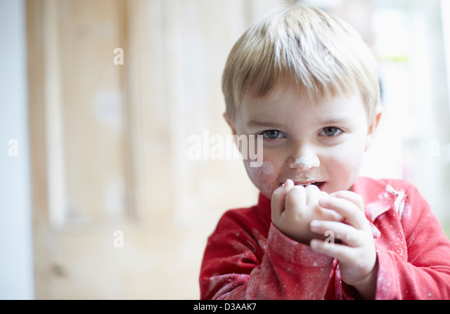Boys face covered in flour in kitchen - Stock Image
