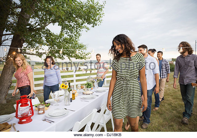 Friends gathering for an outdoor dinner party - Stock Image