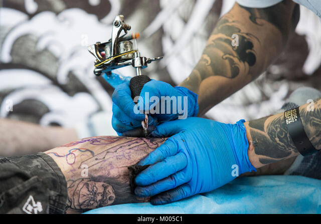 Tattoo artist at work at the Tattoo Convention in Tobacco Dock, London, England, United Kingdom - Stock Image