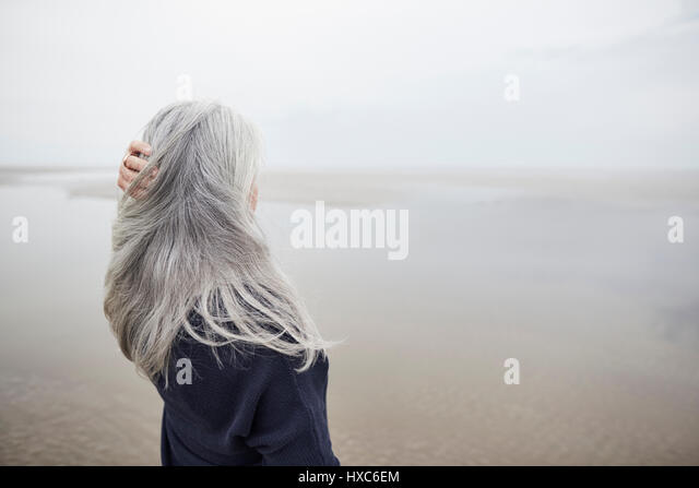 Senior woman with hand in long gray hair on winter beach - Stock Image