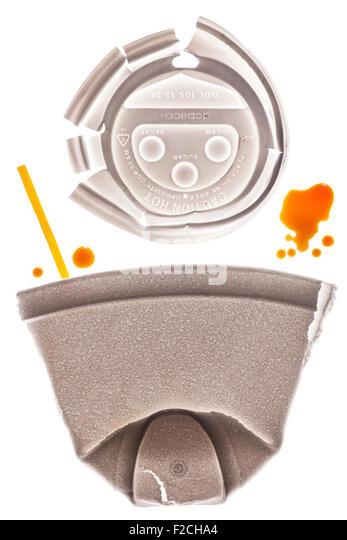 flattened styrofoam coffee cup with cap above and yellow stir stick on light table with drops of coffee - Stock Image