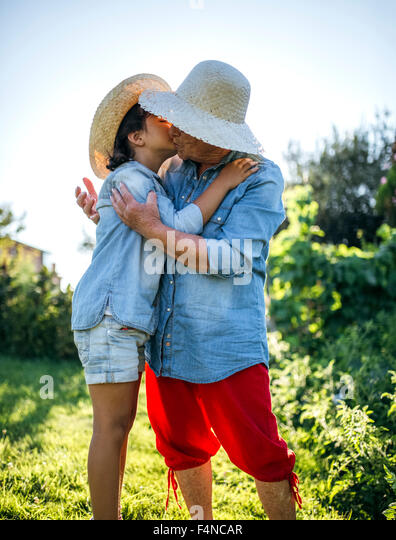 Senior woman hugging and kissing her granddaughter in the garden - Stock Image