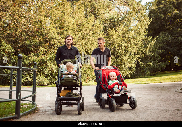 Men pushing babies on baby carriages in park - Stock Image