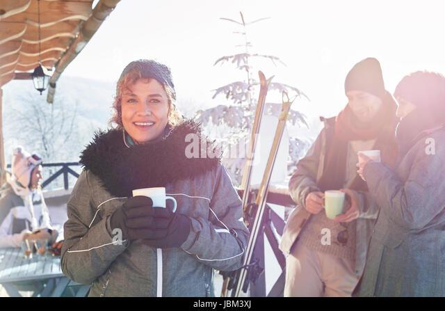 Portrait smiling female skier drinking coffee on cabin deck with friends apres-ski - Stock-Bilder