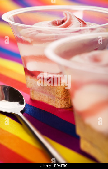 Individual pots of strawberry cheesecake on a multiple coloured background - Stock Image