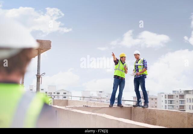 Construction worker and engineer talking at highrise construction site - Stock Image