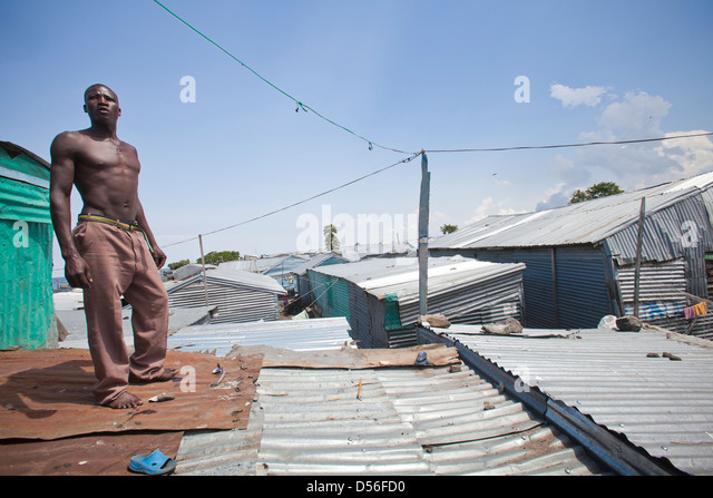 Man standing on corrugated roof in shanty town, Remba Island, Lake Victoria, Kenya. - Stock Image