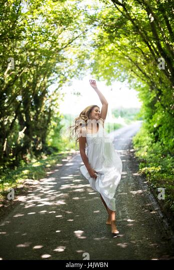 MODEL RELEASED. Young woman in long white dress dancing on country lane. - Stock-Bilder