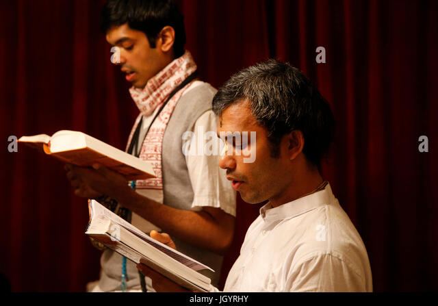 Gita Jayanti celebration in an ISKCON temple. Devotees reading the Bhagavad Gita. Sarcelles. France. - Stock Image