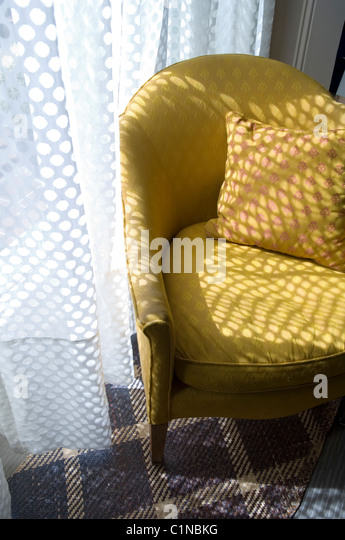 Yellow armchair by spotted net curtain on tartan style carpet - Stock-Bilder